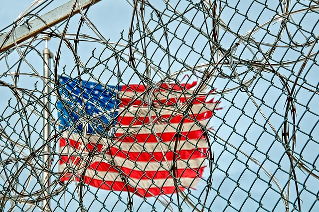 Chain link fencing with barb wire and tattered American flag