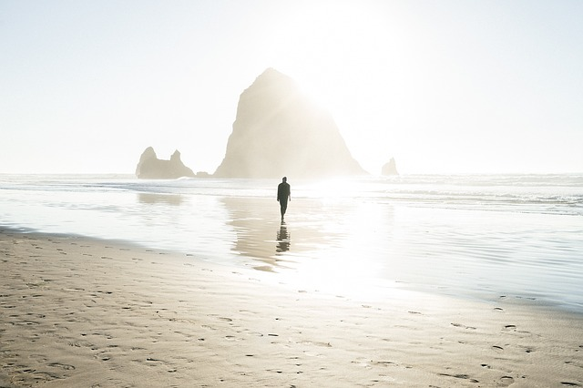 Solitary man walking on a misty beach